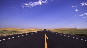 A distant road in the Palouse vanishes off in the distance on a fair, sunny day in Eastern Washington State.